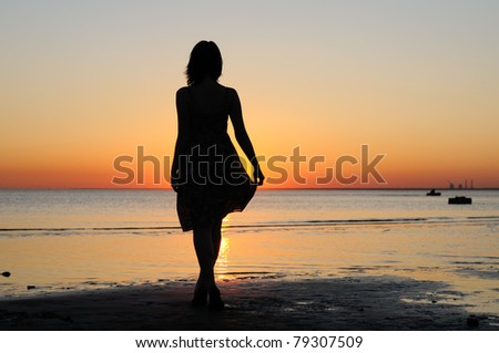 Portrait of young woman as silhouette by the sea - stock photo