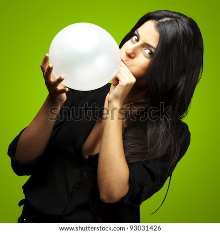 portrait of young woman blowing balloon against a green background