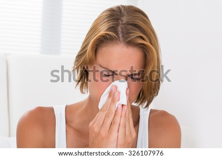 Portrait Of Young Woman Blowing Nose In Tissue Paper