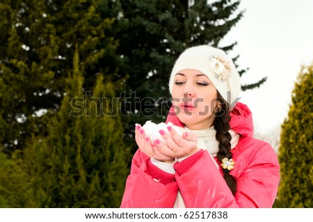 portrait of young woman blowing snow