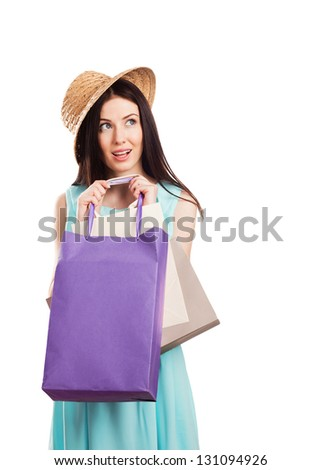 Portrait of young woman carrying shopping bags against white background - stock photo