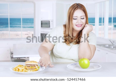 Portrait of young woman choosing fresh apple while refuses hamburger and french fries