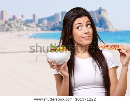 portrait of young woman choosing pizza or salad against a beach