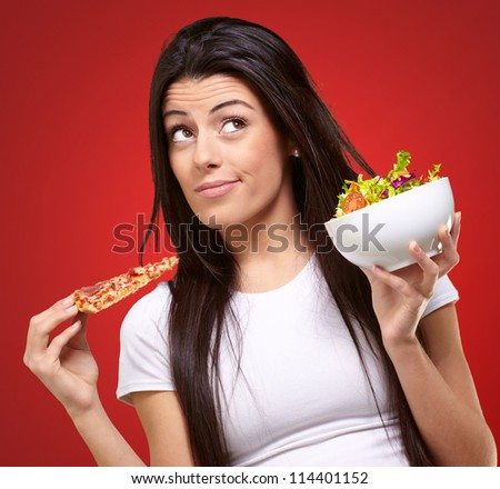 portrait of young woman choosing pizza or salad against a red background - stock photo