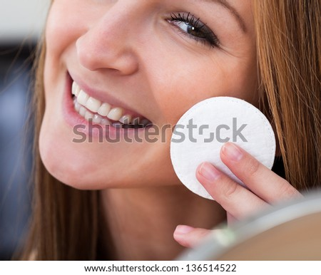 Portrait Of Young Woman Cleansing Her Face With Cotton - stock photo