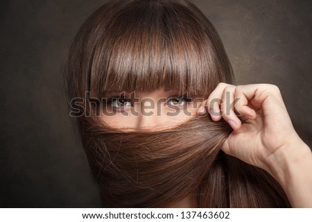 Portrait of young woman closing face by long hair on dark brown background