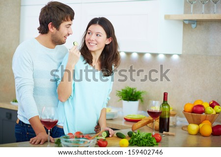 Portrait of young woman cooking salad and looking at her husband in the kitchen  - stock photo