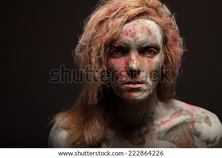 Portrait of young woman covered in healing clay. Mud rich in minerals: calcium, magnesium, sodium, zinc, potassium, iron, etc.