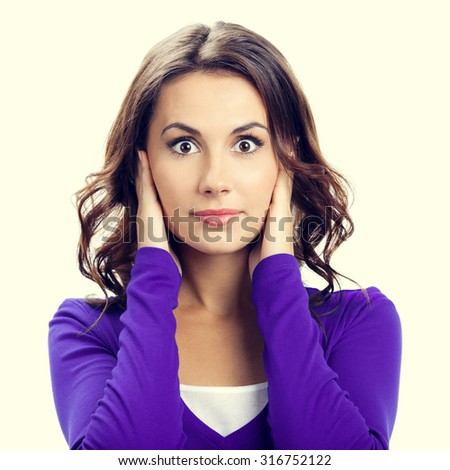 Portrait of young woman covering with hands her ears, in violet casual clothing - stock photo