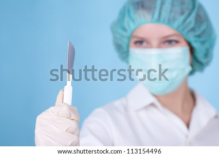 Portrait of young woman doctor surgeon (or nurse) with scalpel. Focused on scalpel.