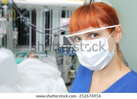 Portrait of young woman doctor with surgical mask and safety glasses in a hospital - stock photo