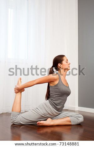 portrait of young woman doing stretch exercise - stock photo