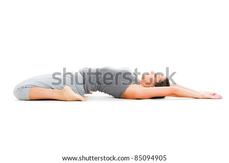 portrait of young woman doing yoga exercise on white floor - stock photo