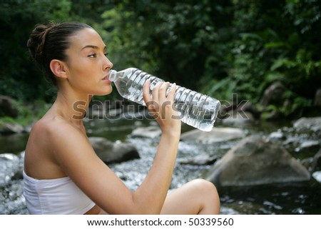 Portrait of young woman drinking water from bottle