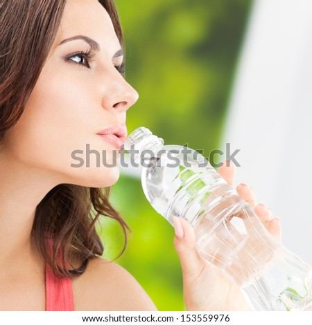 Portrait of young woman drinking water from bottle, outdoors - stock photo
