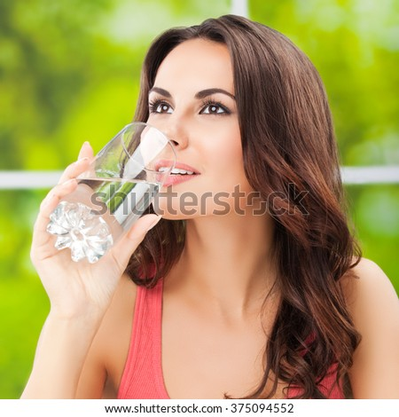 Portrait of young woman drinking water, outdoor - stock photo