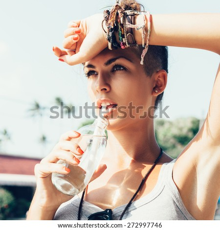 Portrait of young woman drinking water.  Stylish Girl against urban scene - stock photo