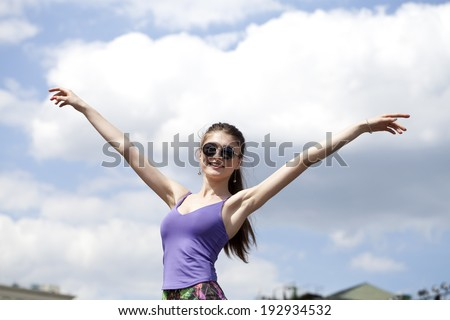 Portrait of young woman enjoying life against the blue sky - stock photo
