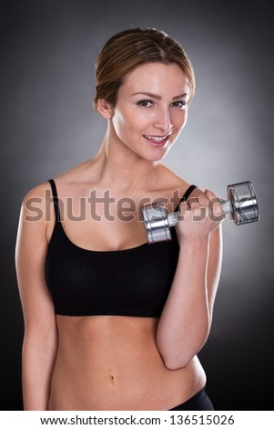 Portrait Of Young Woman Exercising With  Dumbbells - stock photo