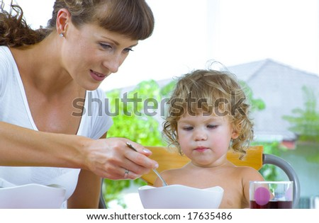 Portrait of young woman feeding her baby daughter