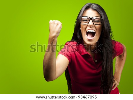 portrait of young woman gesturing victory against a green background - stock photo