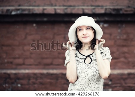 Portrait of young woman. Girl in white hat posing against blurred vintage brick wall background. Selective focus on girl. Toned photo with copy space. Vintage style photo. - stock photo