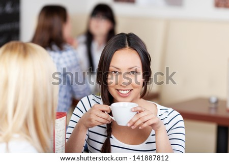 Portrait of young woman having coffee with friend in cafe - stock photo