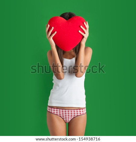 Portrait of young woman hiding behind red heart against green background.  - stock photo
