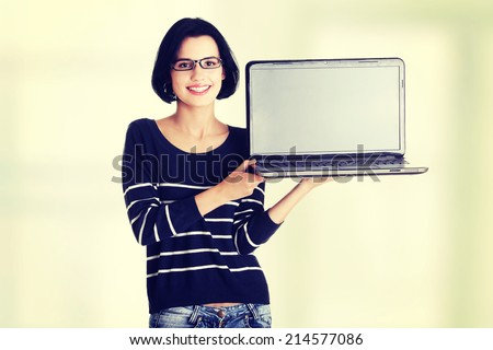 Portrait of young woman holding and showing screen of 17 inch laptop
