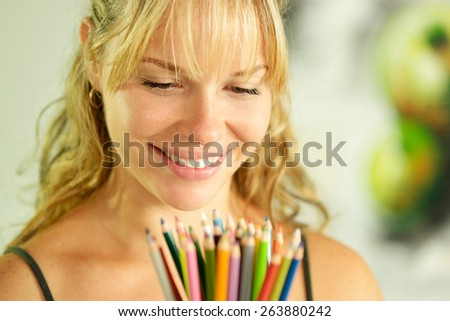 Portrait of young woman holding bunch of colorful pencils at camera and smiling - stock photo