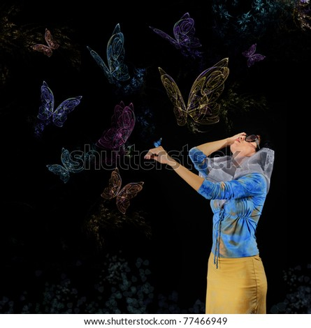 Portrait of young woman holding butterfly and staring at numerous butterflies fliying around - stock photo