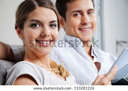 Portrait of young woman holding tablet PC while sitting besides man