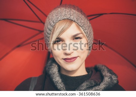 Portrait of young woman holding umbrella - stock photo