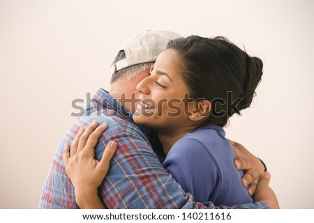 Portrait of young woman hugging her father - stock photo