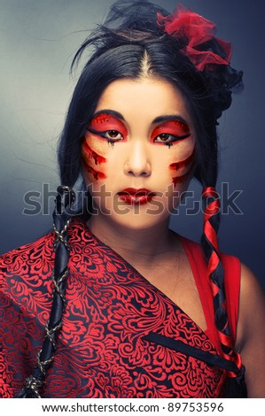 Portrait of young woman in black and red silk  with creative make-up