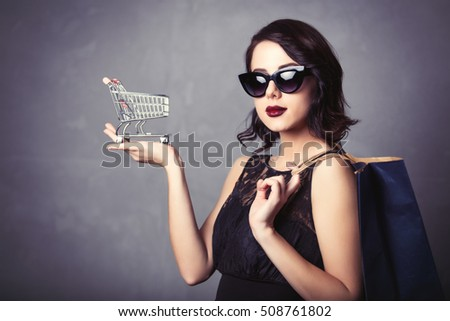 Portrait of young woman in black dress with shopping cart and bag waiting for Black Friday over grey background