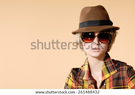 Portrait of young woman in cap with sunglasses  - stock photo