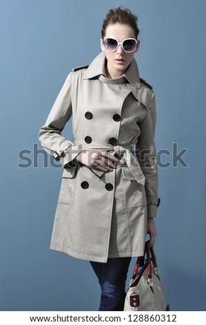 Portrait of young woman in coat with fashion handbag posing