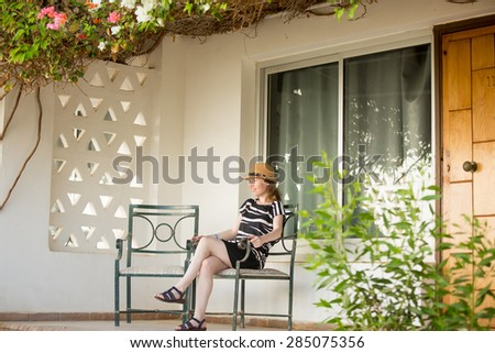 Portrait of young woman in cute straw hat and summer dress sitting on chair on porch of white cottage house covered in flowers, relaxing, dreamily smiling