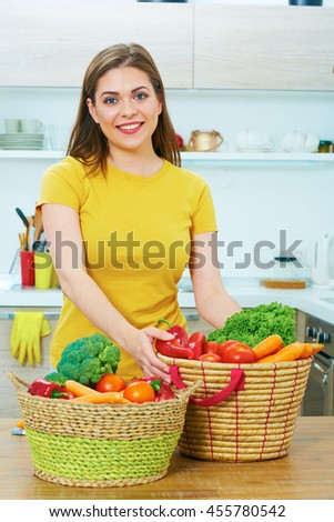 Portrait of young woman in kitchen with vegetables. Healthy food. Vegetables diet. Close up face.
