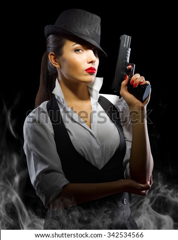 Portrait of young woman in manly style with gun and smoke - stock photo