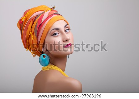 Portrait of young woman in orange shawl and with exotic jewelery - stock photo