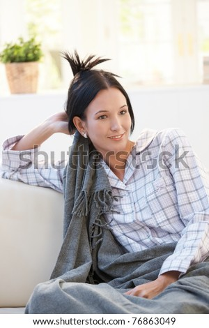 Portrait of young woman in pyjama covered in blanket, sitting in bright living room, smiling.?