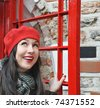 portrait of young woman in red hat look out from phonebox - stock photo