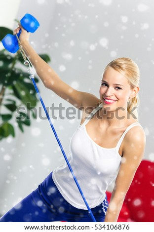Portrait of young woman in sportswear, doing fitness exercise with dumbbell and expander at home. Healthy lifestyle, weight lossing and sporting theme concept shot. Over snow.