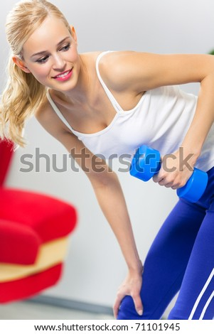 Portrait of young woman in sportswear, doing fitness exercise with dumbbell, indoors
