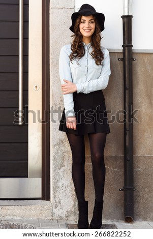 Portrait of young woman in urban background wearing casual clothes and hat - stock photo