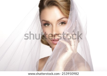portrait of  young woman in wedding dress posing with  bridal veil on white - stock photo