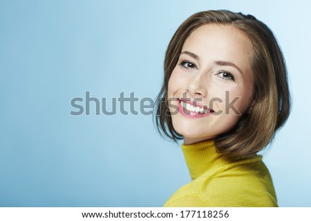 Portrait of young woman in yellow polo neck, smiling