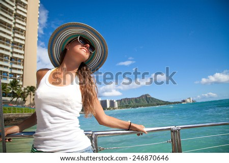 Portrait of young woman leaning on yacht railings, Oahu, Hawaii, USA. Girl on travel vacation holidays relaxing on Hawaiian Waikiki beach with Diamond Head mountain. Summer cruise holidays - stock photo